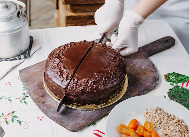 Torta choco che viene tagliata squisita deliziosa rotonda intera progettazione con noci kumquat