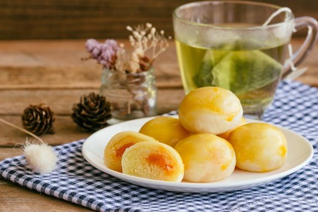 Torta cinese di pasticceria o luna con fagioli mung dolci e uova salate servite con tè verde caldo.