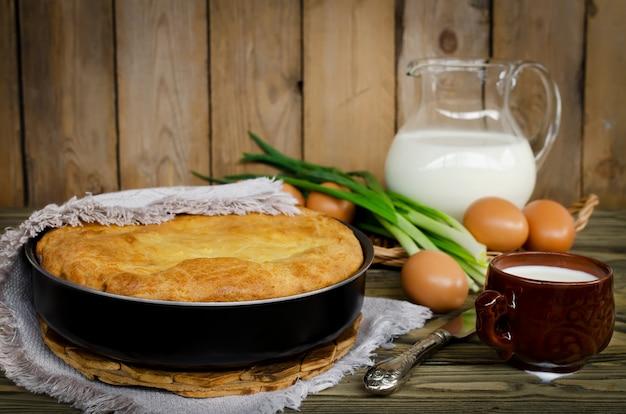 Torta con cipolle e uova sul tavolo di legno