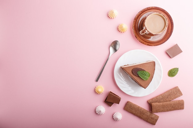 Torta con crema al cioccolato al latte soufflé con tazza di caffè, meringhe su uno sfondo rosa pastello. vista dall'alto, copia spazio.