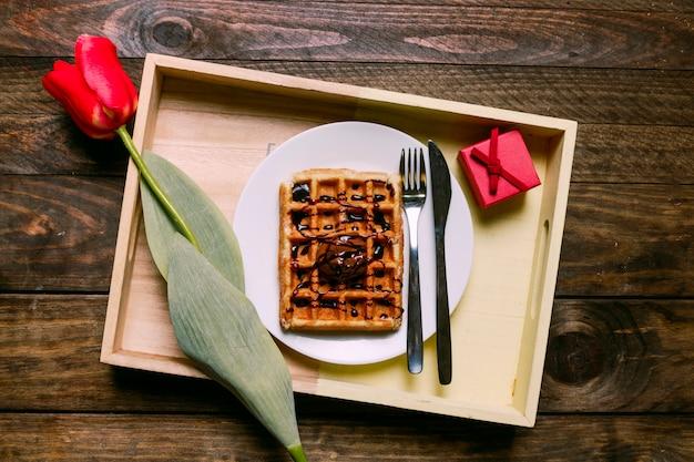 Torta con crema al cioccolato sul piatto con posate vicino fiore e confezione regalo a bordo