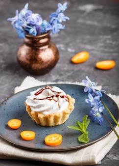 Torta con crema di uova montate su un piatto di ceramica blu con fette di kumquat e foglie di menta su un cemento nero. decorato con fiori blu. vista laterale.
