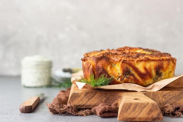 Torta con fegato, uova e aneto ripieno su una tavola di legno.