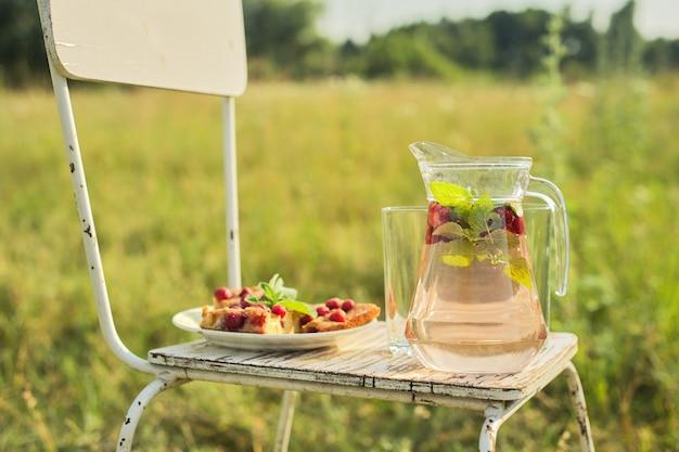 Torta con frutti di bosco e brocca con bevanda alla menta fragola