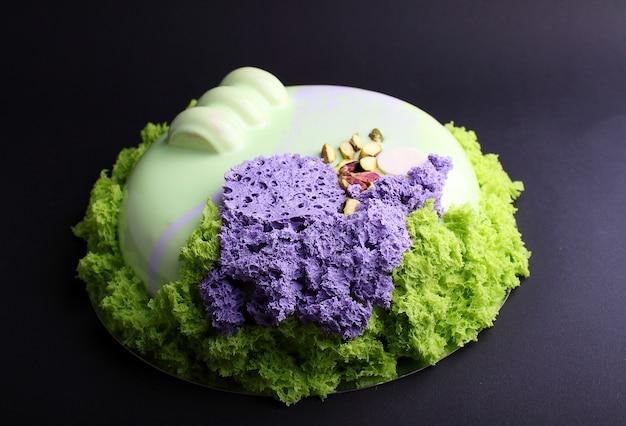 Torta con mousse di frutti di bosco nella glassa a specchio decorata con un biscotto molecolare. sullo sfondo nero