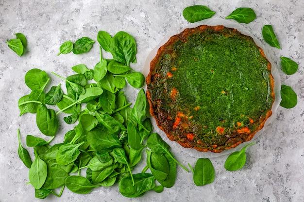 Torta con pesce e spinaci su uno sfondo di pietra chiara