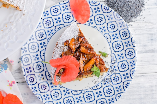 Torta con semi di papavero su uno sfondo bianco. dolci fatti in casa e fiori rossi