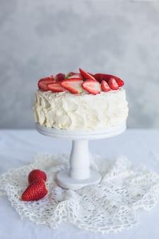 Torta crema bianca con la fragola sulla tabella bianca