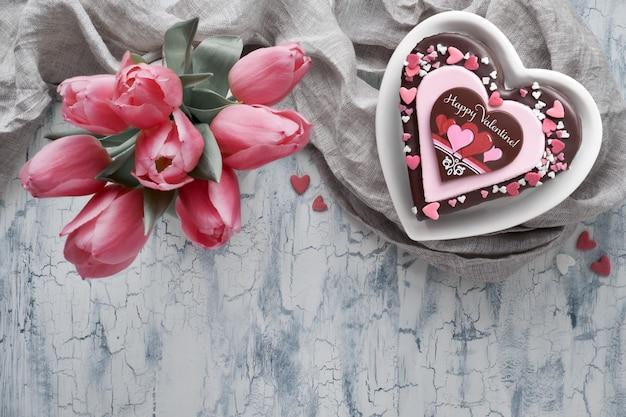 Torta del cuore del biglietto di s. valentino con testo e i tulipani rosa