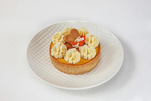 Torta del frutto della passione e mango in cima con una crema rotonda su un piatto bianco rotondo su un bianco isolato