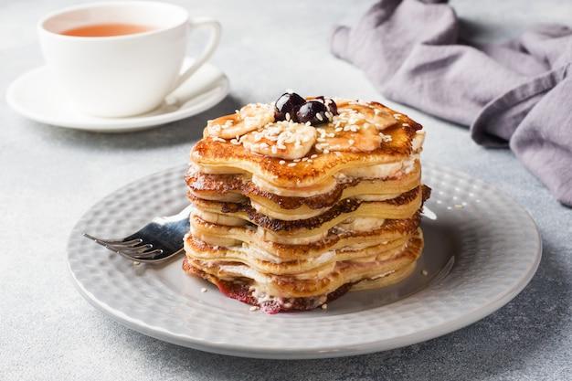 Torta del pancake con lo sciroppo della bacca e delle banane, fuoco selettivo, fondo grigio.