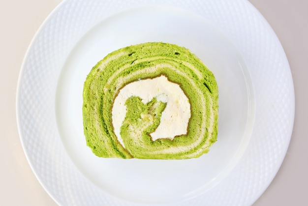 Torta del rotolo dell'igname del tè verde di matcha sul piatto bianco