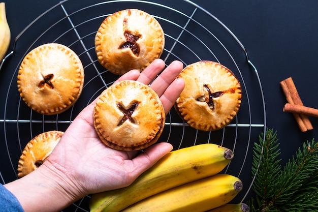 Torta della mano adottiva casalinga al forno fresca fresca della banana di concetto dell'alimento sul nero
