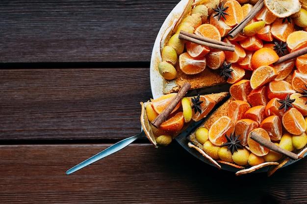 Torta di agrumi vista dall'alto con sfondo colorato di spezie