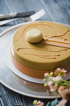 Torta di budino gialla appena sfornata con dacquoise di mandorle, confit di lampone, strato croccante con nocciole caramellate e polvere di lamponi