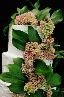 Torta di cerimonia nuziale di lusso decorata con i fiori e le foglie verdi lilla su un fondo nero