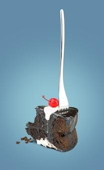 Torta di ciliegia isolata del cioccolato con la forcella dalla parte posteriore su fondo blu.