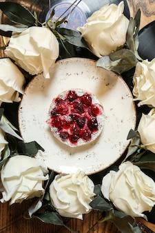 Torta di ciliegie vista dall'alto su un piatto con rose bianche in un cerchio