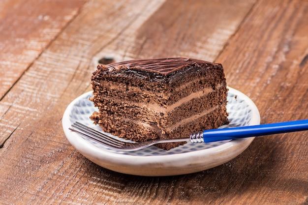 Torta di cioccolato su un piatto su fondo di legno.