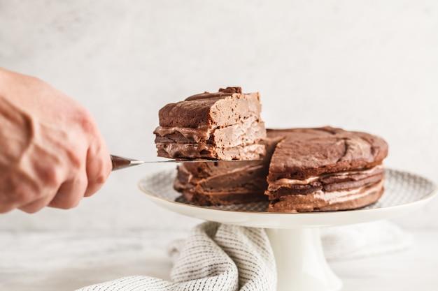 Torta di cioccolato vegan su un piatto bianco per torta, copia spazio, sfondo chiaro.