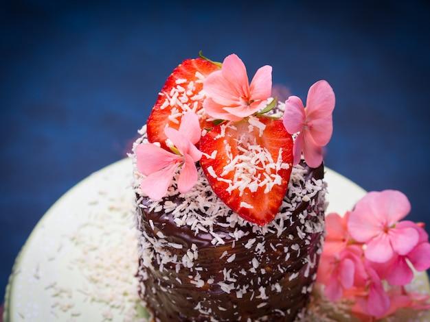 Torta di cocco al cioccolato con decorazioni di fiori di fragola su sfondo blu scuro