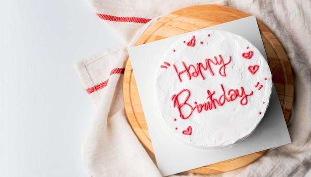 Torta di compleanno bianca e testo di buon compleanno sulla torta.