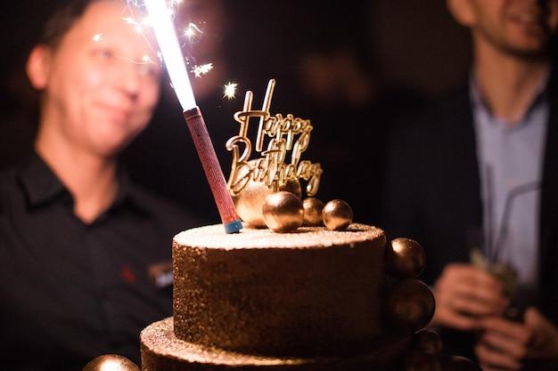 Torta di compleanno con candele, luci luminose bokeh.