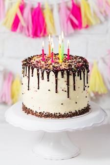 Torta di compleanno con glassa di cioccolato e candele multicolori
