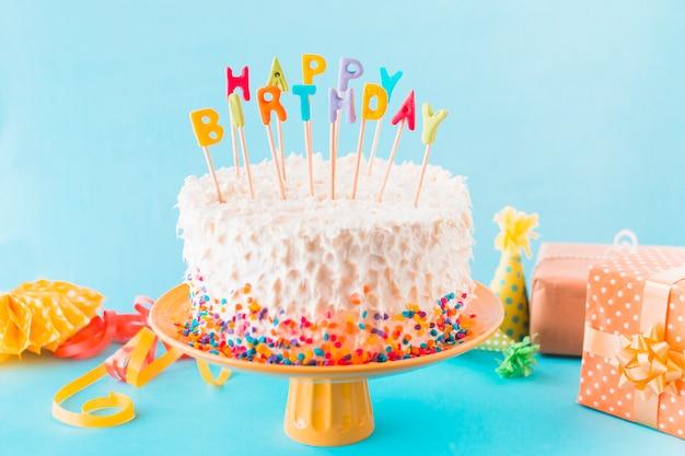 Torta di compleanno con regalo e accessori su sfondo blu