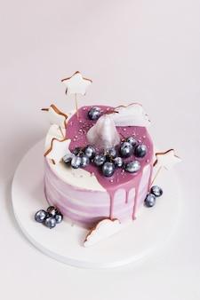 Torta di compleanno decorata con mirtilli e biscotti