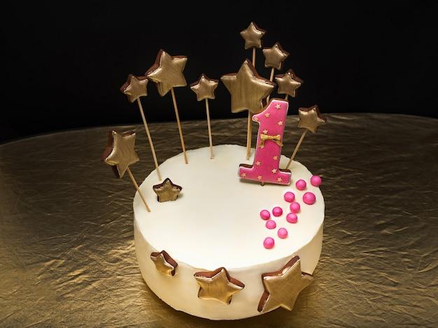 Torta di compleanno decorata con numero rosa 1 e stelle dorate di pan di zenzero su un buio