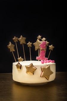 Torta di compleanno decorata con numero rosa 1 e stelle dorate di pan di zenzero