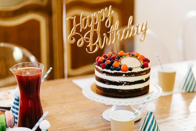 Torta di compleanno deliziosa sulla tavola di legno con i vetri e la composta.
