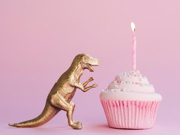 Torta di compleanno e dinosauro divertente su sfondo rosa