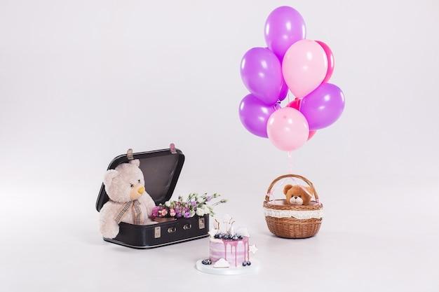 Torta di compleanno, orsacchiotto nel suitecase d'annata e palloni isolati su fondo bianco