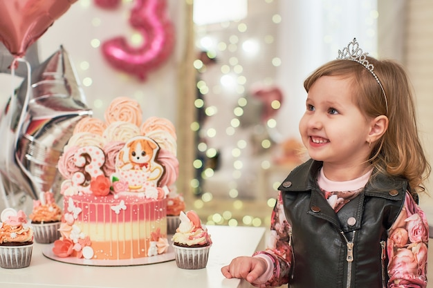 Torta di compleanno per 3 anni decorata con farfalle, gattino di pan di zenzero con glassa e il numero tre.