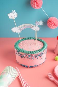 Torta di compleanno per ragazzi e ragazze con bicchieri e cannucce di carta per una festa