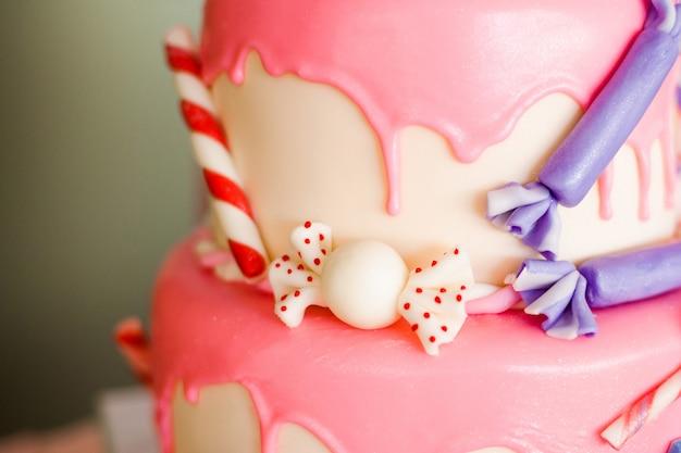 Torta di compleanno rosa con caramelle e lecca lecca pop