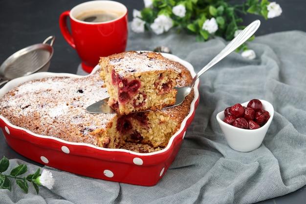Torta di farina d'avena con ciliegia spolverata di zucchero a velo in forma ceramica a forma di cuore