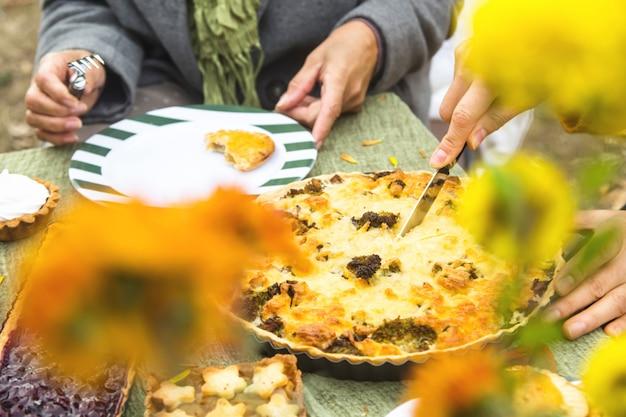 Torta di formaggio abbondante fatta in casa sul tavolo. la donna sta tagliando una torta per la famiglia.