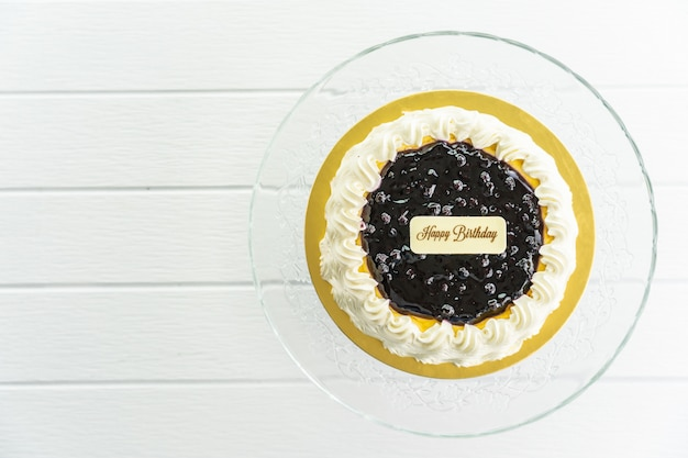 Torta di formaggio ai mirtilli con segno di buon compleanno sulla parte superiore