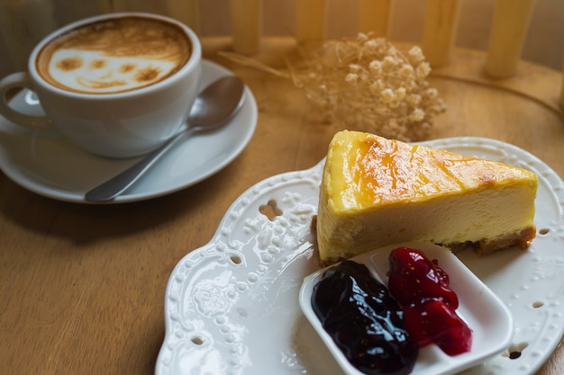 Torta di formaggio con la tazza di caffè caldo sulla tavola di legno