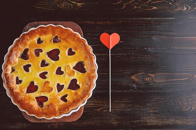 Torta di fragole per san valentino con cuori su un tavolo di legno