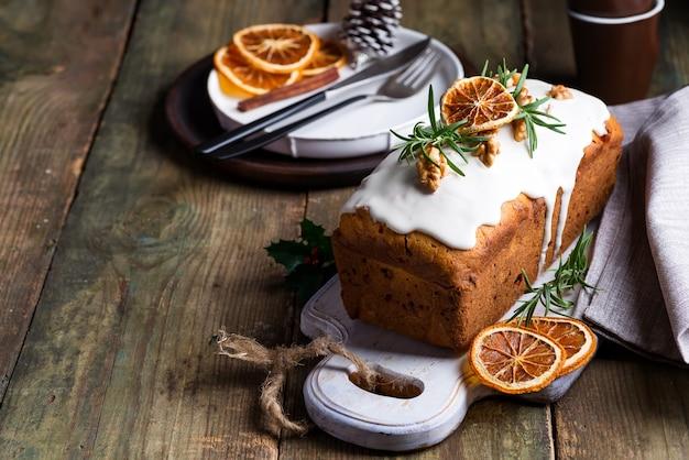 Torta di frutta spolverata di glassa, noci, melograno e primo piano arancione secco. torta fatta in casa di natale e vacanze invernali
