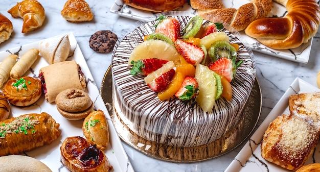 Torta di frutta vista laterale con crema di vaniglia cioccolato kiwi arancione fragola ananas e pasticcini sul tavolo