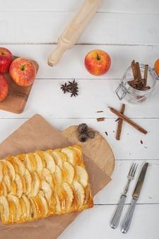 Torta di mele con pasta di brioche sulla tavola di legno rustica bianca. vista dall'alto. immagine verticale.