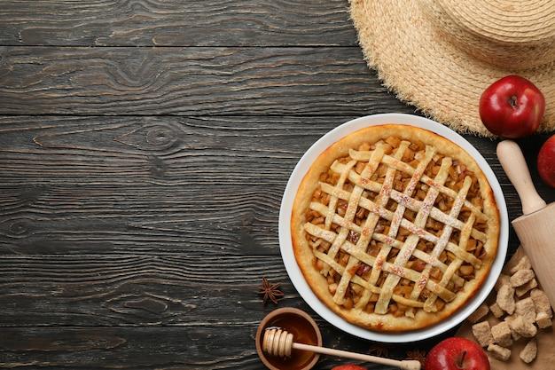 Torta di mele e ingredienti su fondo di legno