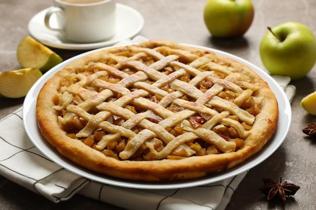 Torta di mele e ingredienti su sfondo grigio