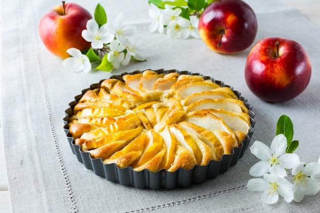 Torta di mele e meli in fiore sul tovagliolo di lino