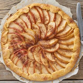 Torta di mele, galette con frutta, dolci pasticcini sul vecchio tavolo rustico in legno